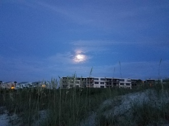 The full moon above the condominiums -- somewhat obscured by clouds.