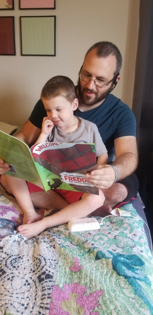 Niko and his father Jim enjoy the illustrated children's book The Many Adventures of Freddie the Circus Mouse by Becky Alexander